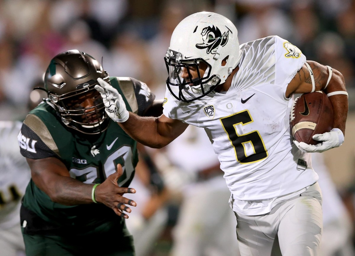 EAST LANSING, MI - SEPTEMBER 12:  Shilique Calhoun #89 of the Michigan State Spartans tries to stop Charles Nelson #6 of the Oregon Ducks during their game at Spartan Stadium on September 12, 2015 in East Lansing, Michigan.  (Photo by Streeter Lecka/Getty Images)