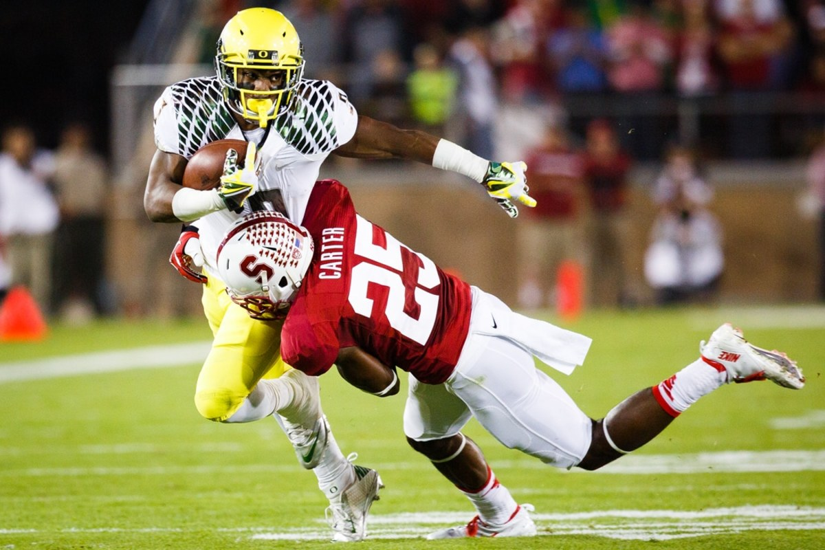 Stanford sophomore cornerback Alex Carter (25) wraps up Oregon sophomore running back Byron Marshall (9) and tackles him to the ground. The No. 3 Oregon Ducks play the No. 5 Stanford Cardinal at Stanford Stadium in Stanford, Calif. on Nov. 7, 2013. (Taylor Wilder/Emerald)