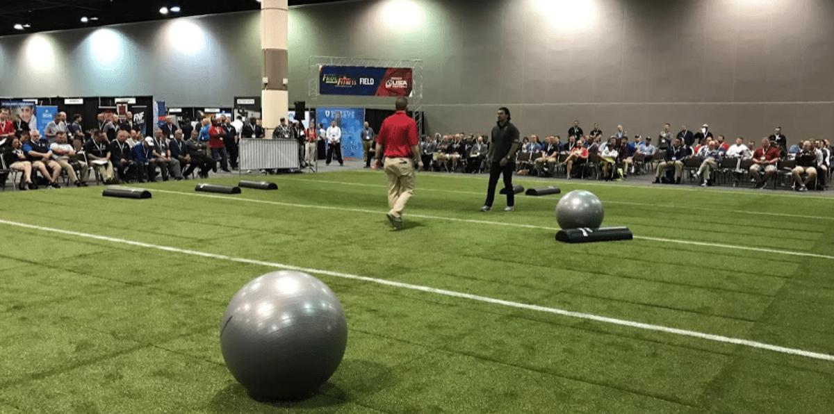 Shoulder tackling demos on field in exhibit hall