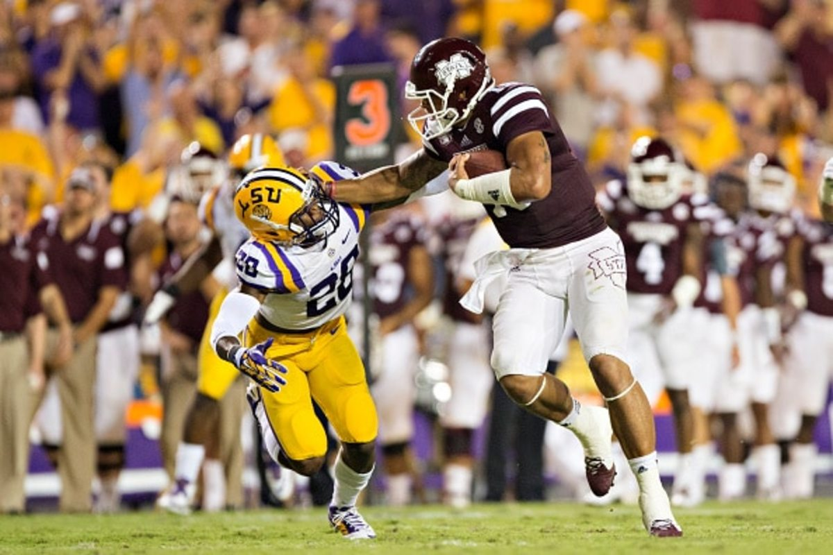 BATON ROUGE, LA - SEPTEMBER 20: Dak Prescott #15 of the Mississippi State Bulldogs stiff arms Jalen Mills #28 of the LSU Tigers at Tiger Stadium on September 20, 2014 in Baton Rouge, Louisiana.  The Bulldogs defeated the Tigers 34-29.  (Photo by Wesley Hitt/Getty Images)